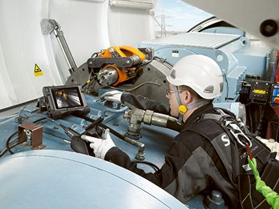Up-tower inspector performing a borescope inspection of the interior of a gearbox in a wind turbine using a portable videoscope.